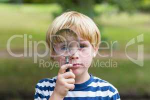 Curious little boy looking through magnifying glass