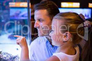 Daughter lookingand father looking at fish in tank