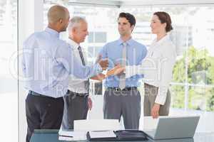 Business team congratulating their colleague
