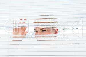 Curious blonde woman looking through venetian blind