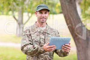 Soldier looking at tablet pc in park
