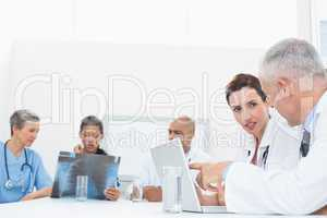 Team of doctors working on laptop and analyzing xray