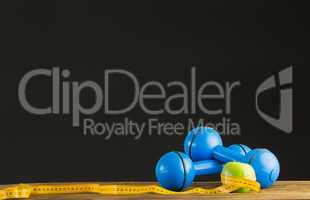 Blue dumbbells with green apple and measuring tape
