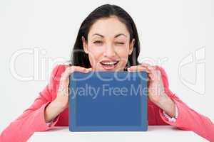 Elegant brunette showing tablet and winking