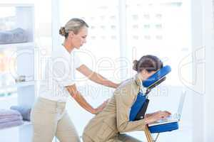 Businesswoman having back massage while using her laptop