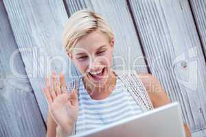 Pretty blonde woman speaking with someone online