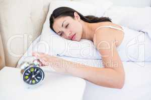 Pretty brunette turning off alarm clock on bed