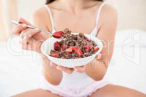 Pretty brunette holding a cereal bowl on bed