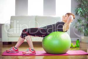 Fit woman doing sit ups on exercise ball