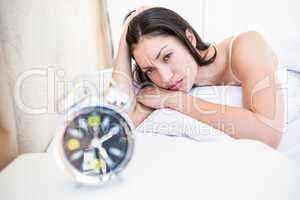 Pretty brunette watching alarm clock on bed