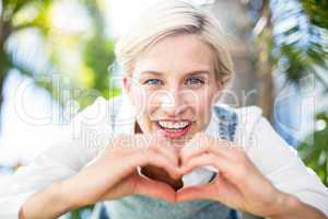 Pretty blonde woman smiling at the camera and doing heart shape