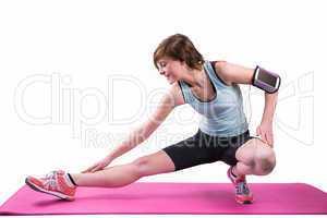 Pretty brunette stretching her leg on exercise mat