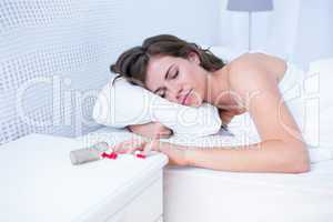 Woman sleeping in bed by spilt bottle of pills on table
