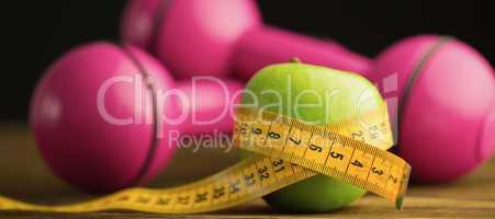 Pink dumbbells with green apple and measuring tape