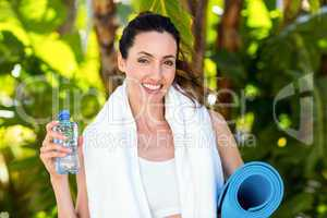 Smiling brunette holding bottle of water and exercise mat