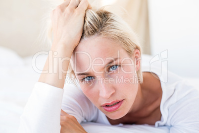 Thoughtful blonde woman lying on the bed