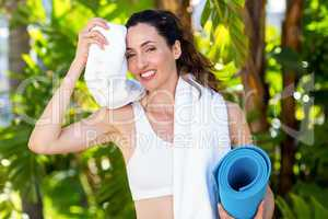 Beautiful brunette holding exercise mat and wiping her forehead