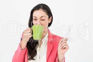 Smiling brunette drinking hot beverage