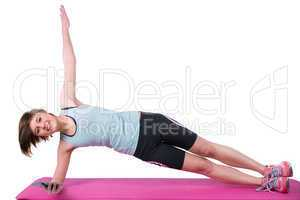 Pretty brunette looking at camera and doing side plank on exerci