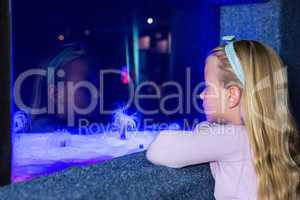 Young woman looking at sea anemone in tank