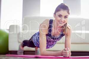 Fit woman planking on exercise mat