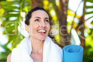 Fit beautiful brunette listening music and holding exercise mat