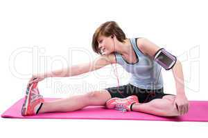 Pretty brunette doing the hamstring stretch on exercise mat
