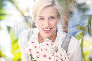 Pretty blonde woman holding bunch of flowers