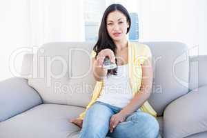 Pretty brunette holding remote control on couch