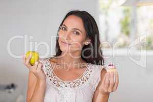 Beautiful brunette holding mini cupcake and an apple