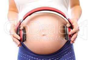 Pregnant woman holding earphones over bump