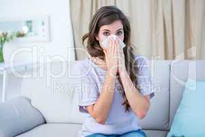 Sick woman blowing her nose looking at camera