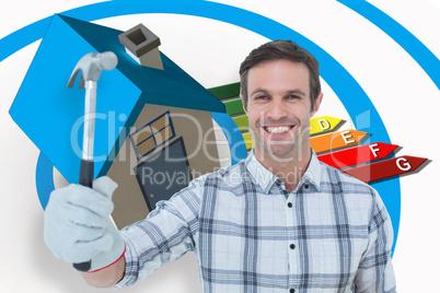 Composite image of happy handyman holding hammer