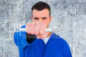 Composite image of confident male mechanic holding spanner