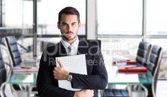 Composite image of businessman in suit posing with his laptop