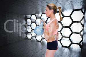 Composite image of female blonde crossfitter lifting kettlebell