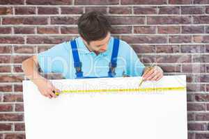 Composite image of carpenter measuring blank bill board