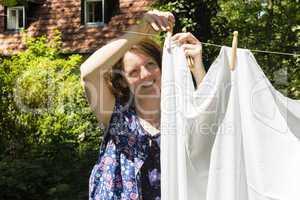 Frau beim Wäscheaufhängen im Garten, Hanging up the washing in
