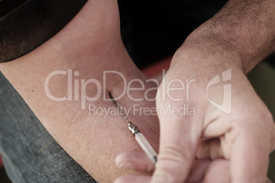 Man injecting himself with a small hypodermic