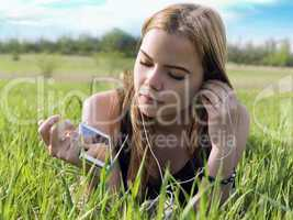 young blond woman listening to music with headphones outdoors