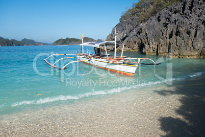 Boat anchored at rocky Coast and Turquoise Waters of Caramoan