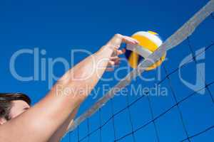 Man throwing volleyball above the net