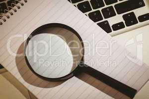 Magnifying glass and notepad on laptop