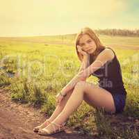 Young sensual smiling blond woman sitting on the grass outdoors