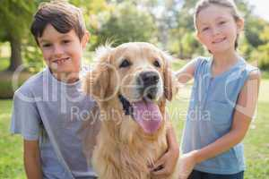 Smiling sibling with their dog in the park