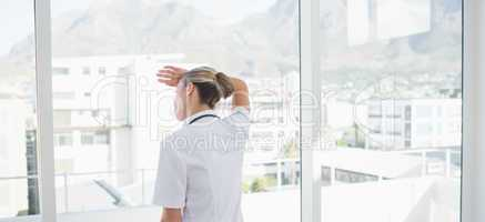 Wear view of confident female doctor looking through windows