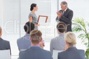 Pretty businesswoman receiving prize