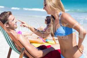 Pretty blonde putting sun tan lotion on her boyfriend