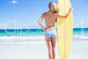 Pretty blonde woman holding surf board