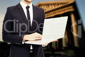 Composite image of mid section of a businessman using laptop